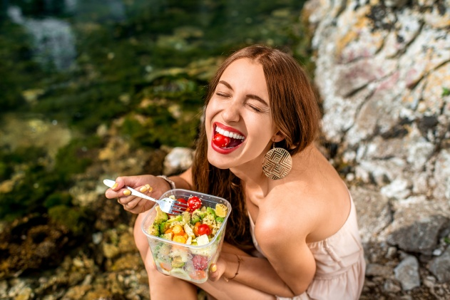 Woman eating healthy salad near the river