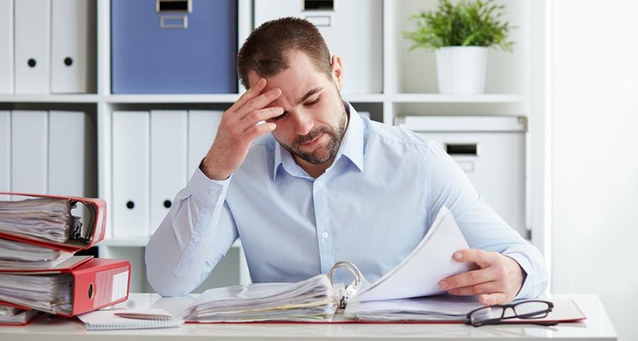 Pensive businessman calculates taxes