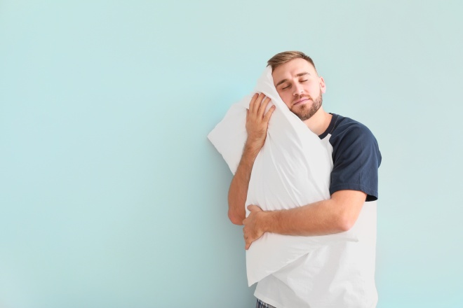Sleepy young man with pillow on light background